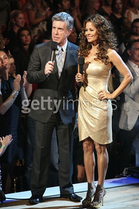 """Brooke Burke, with host Rom Bergeron, wears David Meister's matte gold sequin cocktail dress with side draping on """"Dancing with the Stars"""" on Oct. 18, 2011."""