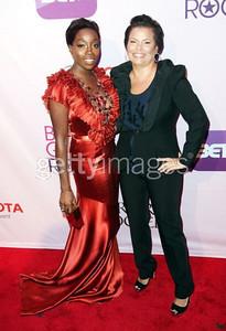 Singer Estelle, with Debra Lee, wears a burnt orange silk gown with Swarovski crystal neckline by Mimi Plange to Black Girls Rock! in New York on Oct. 15, 2011.