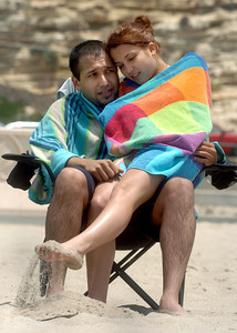 Jessica Pena, 18, of Sunland, and Tito Martinez of Norwalk, cuddle to get warm after swimming at Zuma Beach on Monday, June 25, 2007.  (Tina Burch/Staff Photographer)