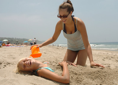 Emma Ryckebosch, 8, of Colorado Springs gets buried by her aunt, Amber Tiffany of Palmdale, at Zuma Beach in Malibu, Ca., on Monday, June 25, 2007.  (Tina Burch/Staff Photographer)
