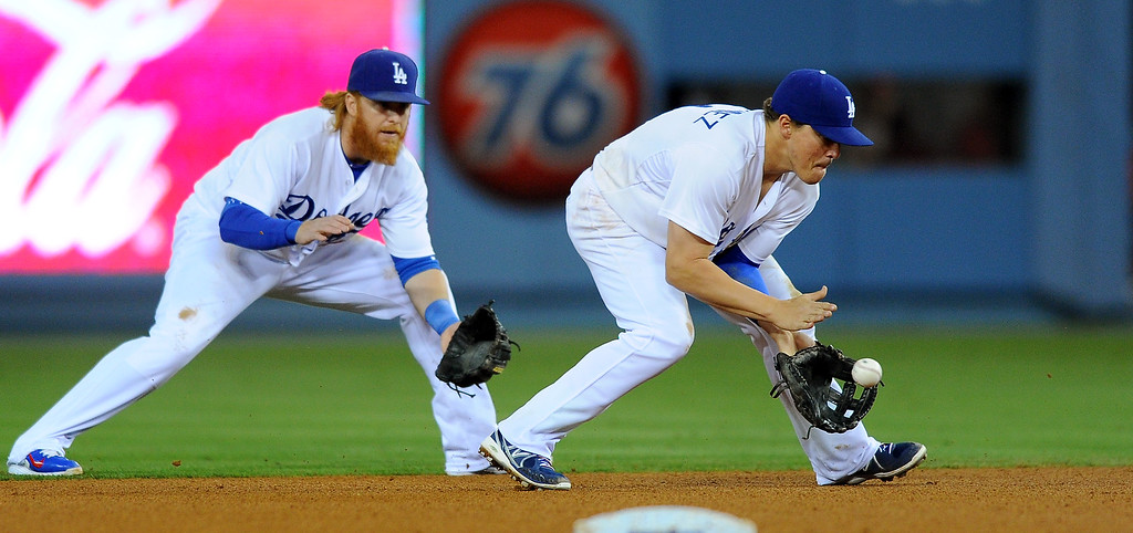 . Dodgers shortstop Enrique Hernandez slides in front of second baseman Justin Turner to field a grounder. (Photo by Michael Owen Baker/L.A. Daily News)