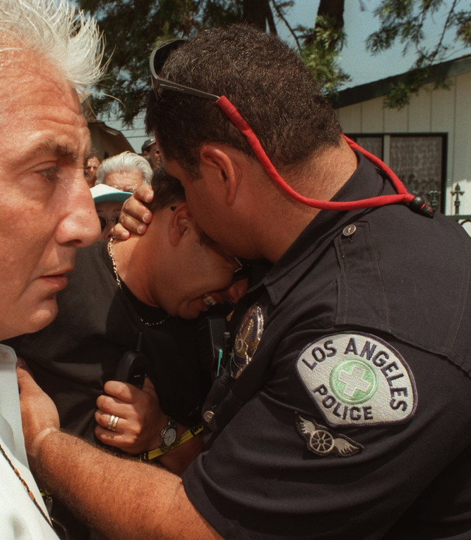 . LAPD officer James LaForce consoles father David Vered as he waits for news about his son, Adir, inside the North Valley Jewish Community Center.  Adir was fine.  Five victims, three male children and two female adults, were shot at the North Valley Jewish Community Center in Granada Hills, California Tuesday morning, August 10, 1999.   Los Angeles Daily News file photo.