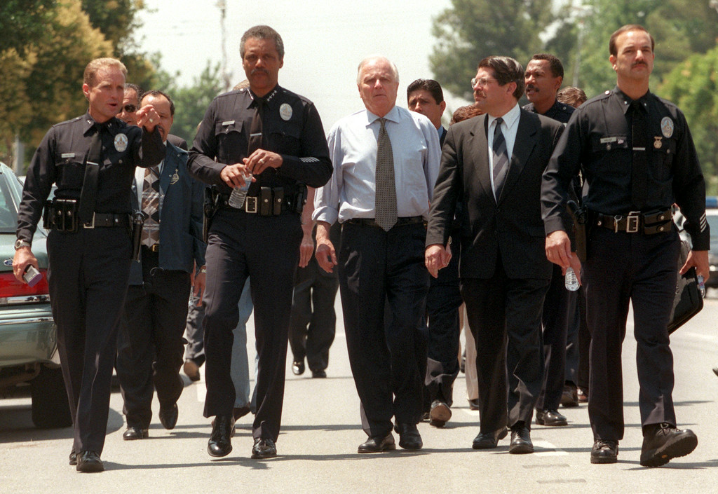 . Left to right, unidentified LAPD officer, LAPD Chief Bernard C. Parks, Los Angeles Mayor Richard Riordan, Supervisor Zev Yaroslavsky, and LAPD Commander David Kalish survey the scene around the North Valley Jewish Community Center in Granada Hills, California, Tuesday, August 10, 1999, where five victims, three male children and two female adults, were shot.   Los Angeles Daily News file photo.