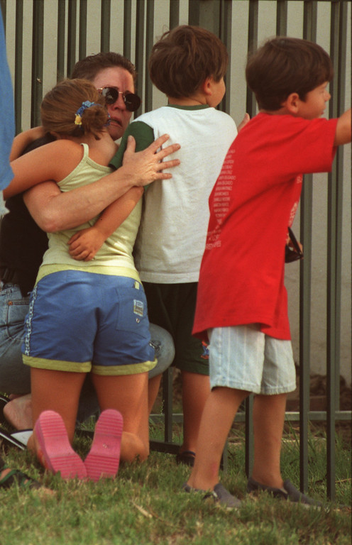 . A parent hugs her  children outside the daycare center of the North Valley Jewish Community Center.  Five victims, three male children and two female adults, were shot in the lobby of the North Valley Jewish Community Center in Granada Hills, California Tuesday morning, August 10, 1999.   Los Angeles Daily News file photo.