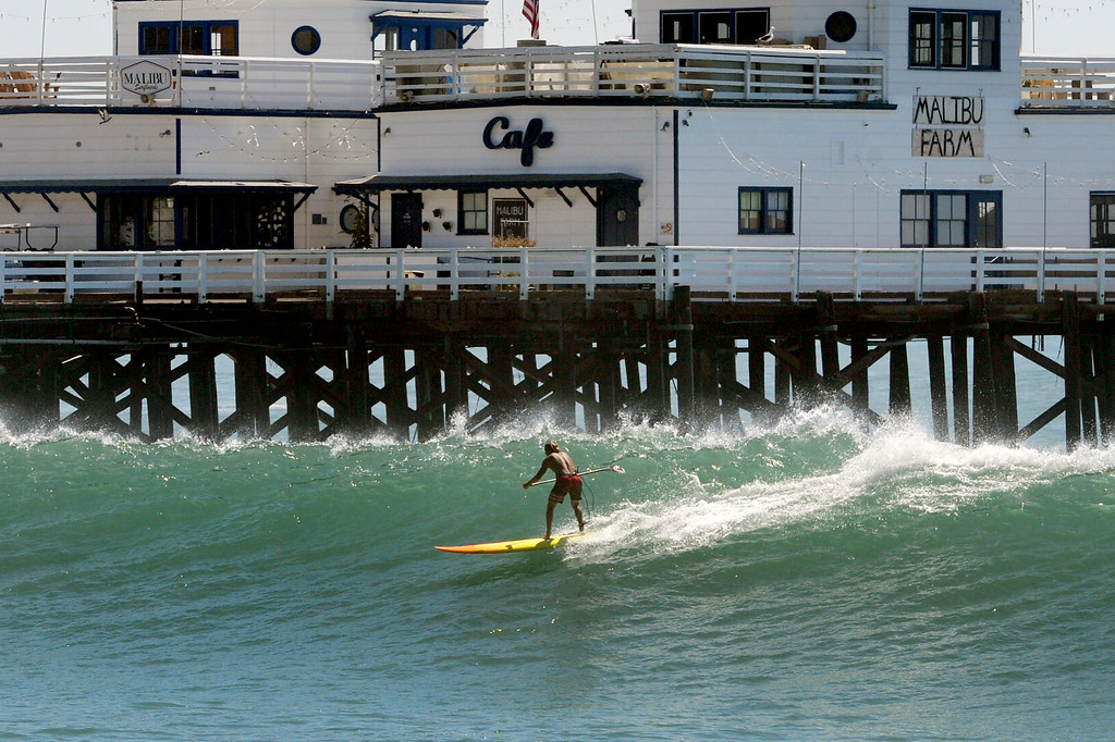 . A paddle boarder rides a wave near the Malibu Pier, Wednesday, August 27, 2014. (Photo by Michael Owen Baker/Los Angeles Daily News)