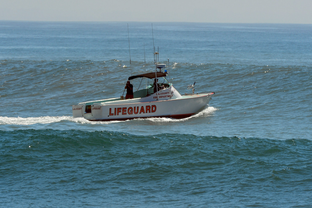 . A Baywatch boat powers through an incoming set at Surfrider Beach in Malibu, Wednesday, August 27, 2014. (Photo by Michael Owen Baker/Los Angeles Daily News)