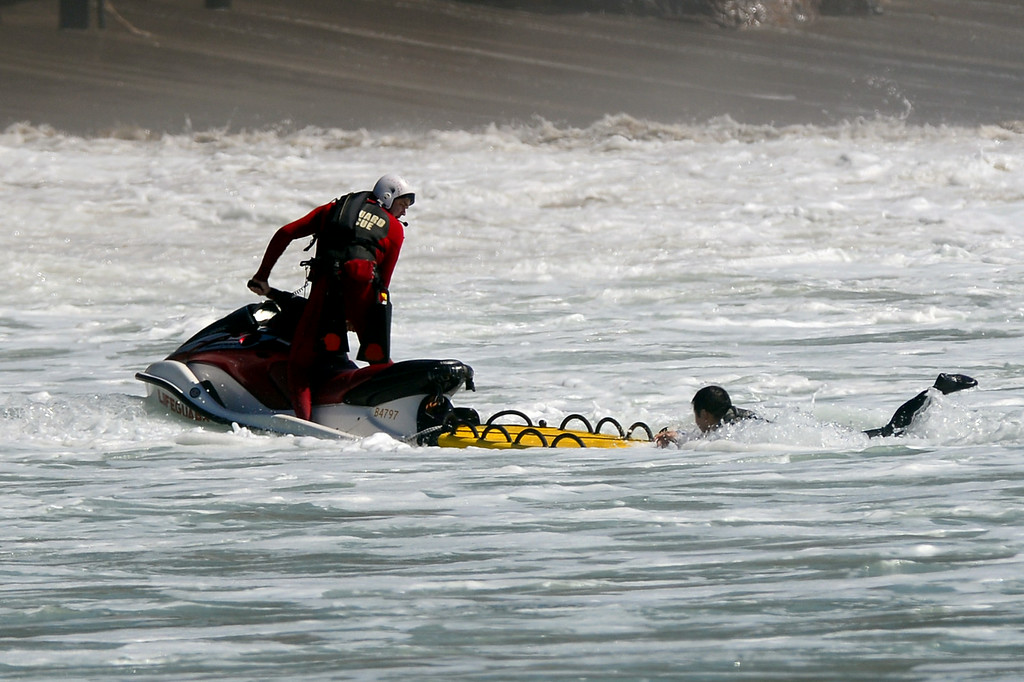 . A lifeguard uses a jet ski to tow a surfer through the impact zone to the beach at Surfrider Beach in Malibu, Wednesday, August 27, 2014. (Photo by Michael Owen Baker/Los Angeles Daily News)