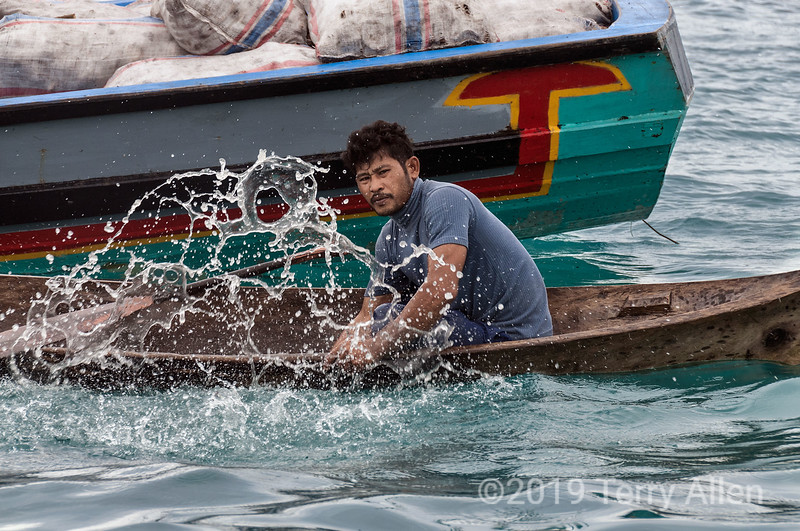 Copra worker bailing out his dugout canoe, Simelulu Island, Sumatra<br /> <br /> Copra is the dried meet of the coconut (call the kernel).  Sacs of coconuts can be seen on the copra boat in the background.  Coconut oil is extracted from the dried coconut meat.