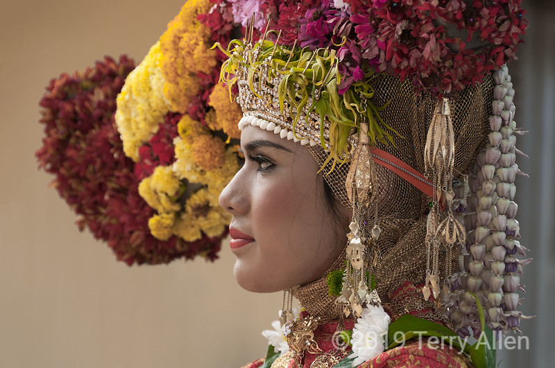 Portrait of an Acehnese woman in elaborate flowered headdress, Banda Aceh, Sumatra<br /> <br /> This photo, and the others in this series, were shot outdoors with natural light and were not posed, but shot as they were seen (with my Nikon D300).  In this case, I noticed her standing in front of a building with a yellow-beige wall that provided a neutral background in an otherwise busy crowd-filled scene.  In situations such as these, when there is lots of light, I usually shoot on aperture priority (at least f11), with the exposure stopped down by one stop to avoid blowing the highlights.