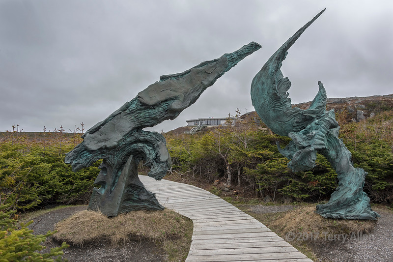L'anse aux Meadows is thought to be the location of the first Viking settlement in North America.  It is a UNESCO World Heritage Site. In this image the visitor center is framed by the 'Meeting of the two worlds' sculpture, completed in two pieces, one by Newfoundland sculptor Luben Boykov and the other by Swedish sculptor Richard Brixel. The two elements of the 3000 pound bronze sculpture symbolically correspond to the geographic points of departure and landing of the Vikings, and their subsequent meeting with Aboriginal peoples. L'anse aux Meadows National Historic Site, Newfoundland.