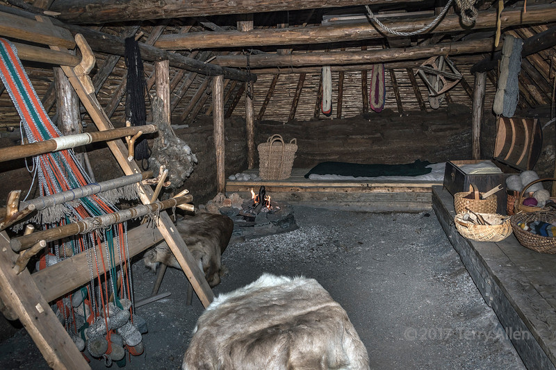 "Women's room with a primitive loom with stone weights, sleeping platforms, a fire pit, and a dirt floor.  This is one of three large rooms in Building F (longhouse) at L'anse au Meadows UNESCO Historic Site, Newfoundland.  The house was reconstructed according the techniques for building sod houses  used when the Vikings settled the area around 1000 AD.<br /> <br /> Sod houses have been built for centuries and examples are known from Norway, Iceland, Ireland and the Canadian and US prairies. An excellent write up on the techniques used in the construction can be found here: <a href=""http://www.hurstwic.org/history/articles/daily_living/text/Turf_Houses.htm"">http://www.hurstwic.org/history/articles/daily_living/text/Turf_Houses.htm</a>.  It was an inexpensive way to built a house on the treeless prairies for the pioneers migrating west.  One Montana settler reported spending only $2.78 on the construction of his entire house.  Because of their thick walls they were cool in summer and warm in winter and completely recyclable.  But because it was built of dirt and grass it was constantly infested with bugs, mice, snakes, and assorted other pests. And the roof could start leaking or even dissolve and collapse in heavy rains.  In very dry weather dirt and grass would start to crumble off the roof and fall like rain inside the house.  Sounds like life in a turf house could be interesting, but challenging."