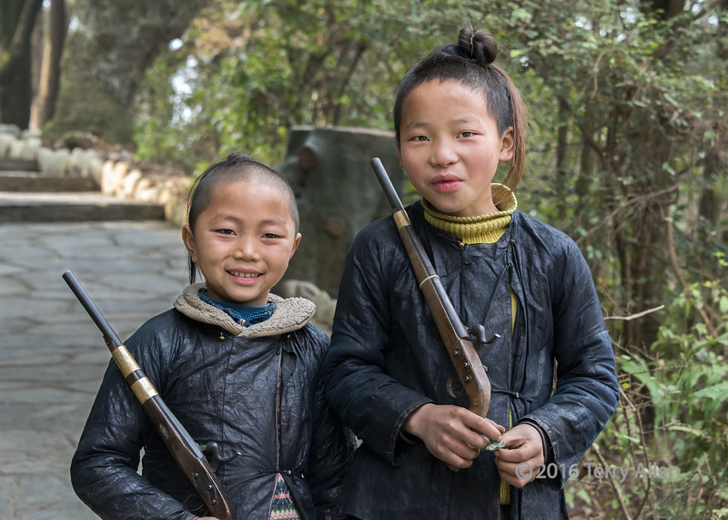 """Ethnic Miao boys from China's only gun village<br /> <br /> Basha village in the southeast of Guizhou province, China, is the home of the last tribe of gunmen in China. The Basha are the only tribe that can legally carry real guns in China. The village is isolated from the outside world and the villagers lead a self-sufficient life in the hilly areas of southern China and retain the dressing and living customs hundreds of years ago. <br /> <br /> Their traditional dress is a hand woven indigo-dyed black cotton made waterproof and shiny by coating with egg white.  The young boys have their heads shaven at around 7 to 15 years of age leaving just a long shank of hair that is twisted into a topnot.  <br /> <br /> The villagers worship trees as gods. They believe the topnots on their heads represent trees, while the purple-brown clothes they wear represent bark. <br /> <br /> All the men carry long flintlock rifles that they shoot in welcoming ceremonies for visitors, and these young boys, dressed in traditional attire, are carrying a shorter version of the guns.<br /> <br /> Other photos from the Miao Basha village can be seen here: <a href=""""http://goo.gl/63lGDV"""">http://goo.gl/63lGDV</a><br /> <br /> 11/04/15  <a href=""""http://www.allenfotowild.com"""">http://www.allenfotowild.com</a>"""