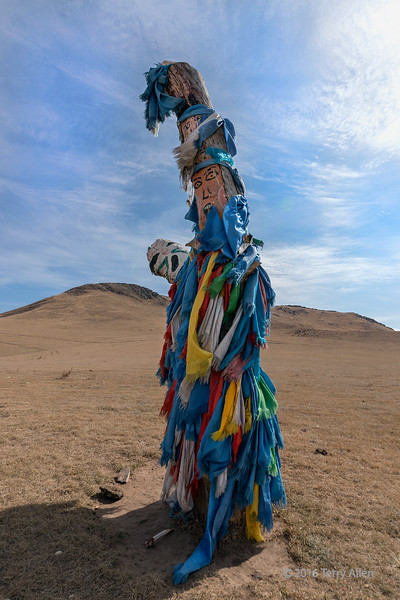 """Shamanic figure<br /> <br /> I learn so much when I travel and take photos.  The things I see prompt me to do a lot of research to understand the significance of what I am photographing.  Stopping at a roadside shrine in Mongolia prompted me to learn more about the fascinating religion of Tengriism. <br /> <br /> This figure is from a religion known as Tengriism,  practised by the people in Central Asia, including Mongolia.  The religion dates from ancient times, and focuses on living in harmony with the natural universe. Tengriism revolves around the sun deity Tengri, and focuses on balance with nature.  Tengriism is believed to have begun sometime around the Bronze Age (3,300 B.C. to 1,200 B.C)., and is one of the world's oldest religions. It incorporates characteristics of shamanism, animism, totemism, both polytheism and monotheism, and ancestor worship. Those who practice Tengriism hold the belief that their very existence is sustained by the spirit of the blue Sky (Tengri), and the fertile Mother Earth (Eje).  The blue scarfs symbolise the sky.<br /> <br /> An ovoo shrine can be been here, along with an explanation of its symbolism and current practices: <a href=""""http://goo.gl/pDzkFI"""">http://goo.gl/pDzkFI</a><br /> <br /> 14/02/15  <a href=""""http://www.allenfotowild.com"""">http://www.allenfotowild.com</a>"""