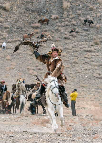 """Competing with flair (best larger)<br /> <br /> Eagle Festival, Olgii, Western Mongolia<br /> <br /> At the Eagle Festival, during the compeition for best eagle, costume and horse, the favorites of the crowds and judges were the competitors that rode fast and held their eagles high with their wings spread (actually riding fast and holding the eagles up causes them to lift their wings to help them balance).  This guy was one of the best at this, and his white horse was magnificent.<br /> <br /> Other images of several of the competitors can be seen here: <a href=""""http://goo.gl/SmHPGM"""">http://goo.gl/SmHPGM</a><br /> <br /> 29/06/15  <a href=""""http://www.allenfotowild.com"""">http://www.allenfotowild.com</a>"""