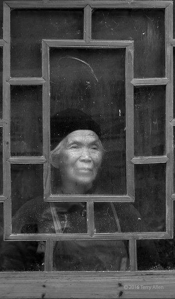 """Old woman, dirty window, cold day BW<br /> <br /> You can see how the lower part of the central panel is starting to get fogged up by her breath on a cold drizzly day.  Shiqiao Miao Village, Guizhou Province, China<br /> <br /> The colour version can be seen here (which do you prefer?), as well as some images of women in traditional attire: <a href=""""http://goo.gl/PxfxR7"""">http://goo.gl/PxfxR7</a>"""