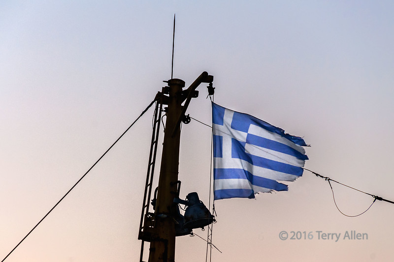 """Tattered Greek flag, Itea, Greece<br /> <br /> This image of a tattered Greek flag, taken on a ship at sunrise, for me is a statement about the battered state of the Greek economy and the fight of the Greek people to rise above their desperate circumstances.<br /> <br /> 09/07/15  <a href=""""http://www.allenfotowild.com"""">http://www.allenfotowild.com</a>"""