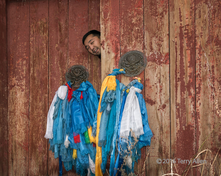 """Prayer shawls and smiling face<br /> <br /> The outer door to Manzushir Monastery festooned with prayers shawls, Bogd Khan Mountains, Mongolia<br /> <br /> This small monastery was rebuilt in recent years after the destruction of the huge Buddhist monastery complex of over 20 temples and 300 monks by the Mongolian Communists in the 1937.<br /> <br /> Other shots of the monastery complex can be seen here: <a href=""""http://goo.gl/0W8b6q"""">http://goo.gl/0W8b6q</a><br /> <br /> 01/02/15  <a href=""""http://www.allenfotowild.com"""">http://www.allenfotowild.com</a>"""