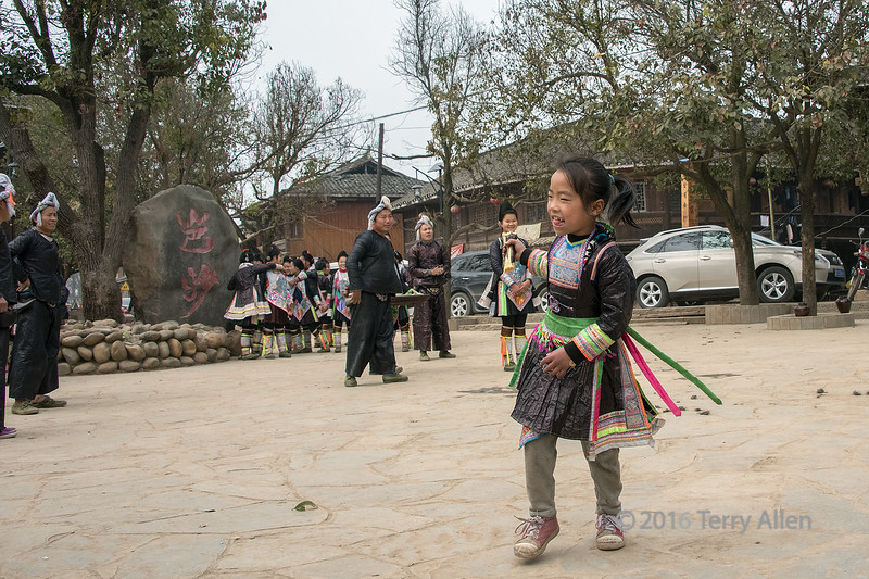 Basha village square with a small girl dancing<br /> <br /> Basha Miao village, Guizhou Province, China