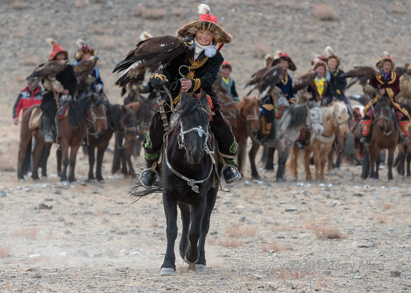 """Pulcritudinous (beautiful, comely) girl: Ashol Pan, Mongolia's only female eagle hunter  (best larger)<br /> <br /> The second contest of the day at the Eagle Festival was for the best Kazakh eagle, costume and horse harness.  Ashol Pan is riding over to the judges, with the rest of the field waiting their turn in the rear.<br /> <br /> Other photos from the Eagle Festival can be seen here: <a href=""""http://goo.gl/82dsNB"""">http://goo.gl/82dsNB</a><br /> <br /> 26/06/15  <a href=""""http://www.allenfotowild.com"""">http://www.allenfotowild.com</a>"""