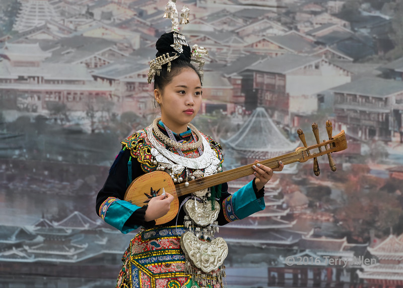 """Portrait of a Dong woman in traditional attire playing a pipa.<br /> <br /> Zhaoxing Dong village, Guizhou Province, China.  This woman is playing a Dong pipa, a four or 5 string plucked instrument.  Her hairstyle is a typical Dong style consisting of a topnot worn high on the head.<br /> <br /> Note: the background is painted on a wall behind her; I desaturated it a little to not be too distracting. You can see the BG better in one or two of the photos accessed from the link below. The jewelry is silver, so probably a bit heavy (but not as heavy as gold).<br /> <br /> The south of China has a number of Chinese minority ethnic groups living in Guizhou and Yunnan provinces.  The Dong are one of the 56 minority groups recognized by the People's Republic of China.  They are skilled carpenters, building unique stilt houses and other wooden structures like drum towers and wind and rain bridges. <br /> <br /> A photo and explanation of their unique stilt house buildings, plus other interesting info about the Dong, can be seen here: <a href=""""http://goo.gl/Gr5b3g"""">http://goo.gl/Gr5b3g</a><br /> <br /> 23//02/15  <a href=""""http://www.allenfotowild.com"""">http://www.allenfotowild.com</a>"""