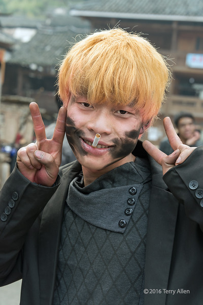 """Happy 4th of July!<br /> <br /> Bleached blonde Dong youth covered with firecracker soot, making peace sign, Huanggang Dong Village, Guizhou Province, China<br /> <br /> Other photos from the Dong Village can be seen here: <a href=""""http://goo.gl/OclgZC"""">http://goo.gl/OclgZC</a><br /> <br /> 04/07/15  <a href=""""http://www.allenfotowild.com"""">http://www.allenfotowild.com</a>"""