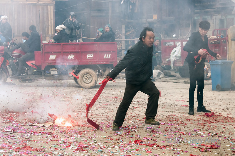 """Pyrotechnic cacophony 'fireworks, bangers' and 'a harsh, discordant mixture of sounds'<br /> <br /> Running with live fireworks, Huanggang Dong Village, Guizhou Province, China<br /> <br /> After the parade of wedding gifts, the festivies degenerated into a loud, ear splitting cacophony, and a seemingly random unorganized fireworks frenzy.  A popular 'trick' was lighting the end of a long red string of firecrakers and running down the street dragging the exploding string, as seen here. <br /> <br /> Other photos of the somewhat dangerous 'festivities' can be seen here: <a href=""""http://goo.gl/pFpaz2"""">http://goo.gl/pFpaz2</a><br /> <br /> 03/07/15 www allenfotowild.com"""