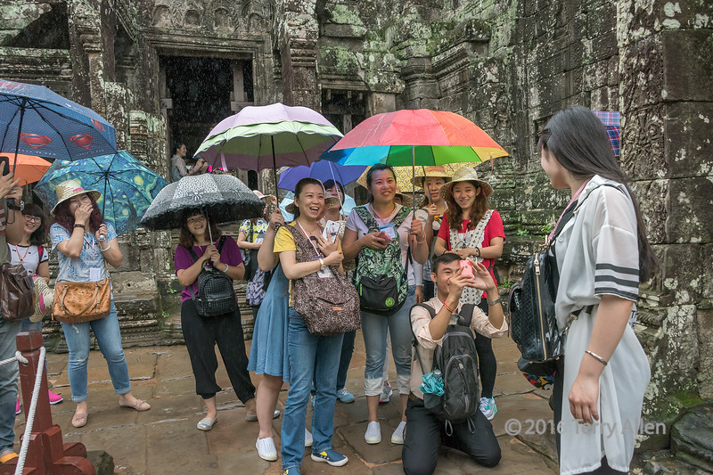 """As I travel around the world, I notice how the culture of travel is rapidly changing, with people travelling in larger groups, that are noisier, with less consideration for others, and more interest in having their photo taken in front of something , and little interest in the thing itself. This photo was taken at Bayon Temple in Siem Reap, and after having my photo taken numerous times (with my consent) by the tourists there, I decided that turn about was fair play.  Notice that they all have their backs to the temple.<br /> <br /> 09/11/15  <a href=""""http://www.allenfotowild.com"""">http://www.allenfotowild.com</a>"""