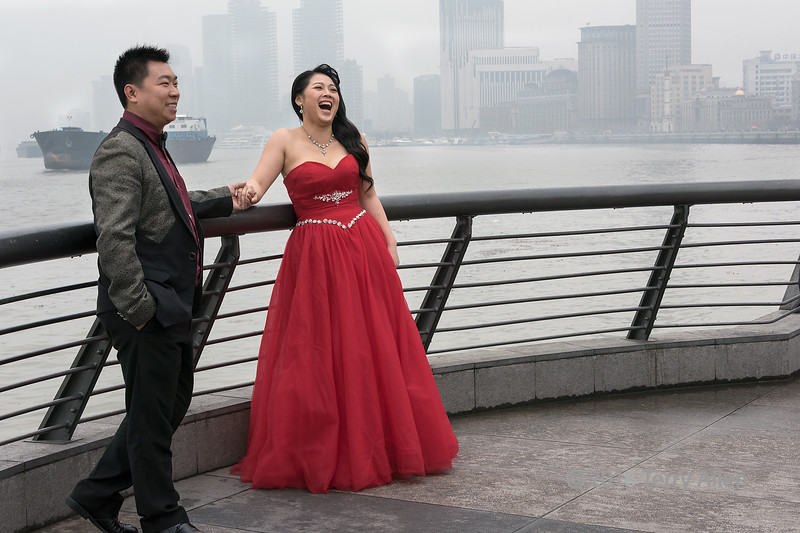 """Wedding couple on The Bund<br /> <br /> It is very traditional for Chinese couples to go to The Bund for their wedding photos, with the Huangpu River and the Pudong skyline in the background.  The Bund is a promenade along the Huangpu river, in the area of the former historic foreign concessions in Shanghai, across the river from the famous Pudong skyline. Chinese couples often have two weddings, a traditional Chinese wedding where the bride wears red, and a western style wedding where the bride wears white. <br /> <br /> Other wedding photos, the Pudong skyline in the fog, and boat traffic on the Huangpu River can be seen here: <a href=""""http://goo.gl/zjW21Y"""">http://goo.gl/zjW21Y</a><br /> <br /> 09/02/15  <a href=""""http://www.allenfotowild.com"""">http://www.allenfotowild.com</a>"""