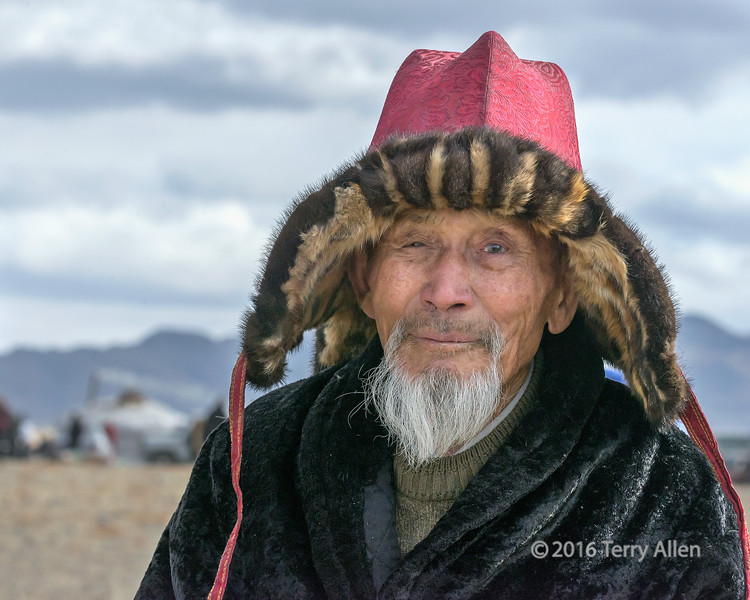"""The eagle hunter<br /> <br /> A portrait of one of the respected old Kazakh eagle hunters with his traditional hat made of red silk brocade and trimmed with the skin from the front legs of hunted foxes. The rest of the fox is not wasted but used for clothing and food. He has a lovely smile and a face full of characer!<br /> <br /> Several photos of the Shyrga Tartu compeition to lure the golden eagle can be seen here (all best larger): <a href=""""http://goo.gl/Qgvi9N"""">http://goo.gl/Qgvi9N</a><br /> <br /> 06/08/15  <a href=""""http://www.allenfotowild.com"""">http://www.allenfotowild.com</a>"""