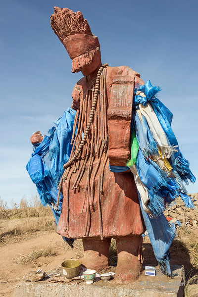 The shaman<br /> <br /> Mongolian Tengerism shaman statue with blue silk prayer scarves (representing Tengri, the god of the sky) and offerings of money, food and cigarettes.  Taken near Ulaanbaatar, Mongolia