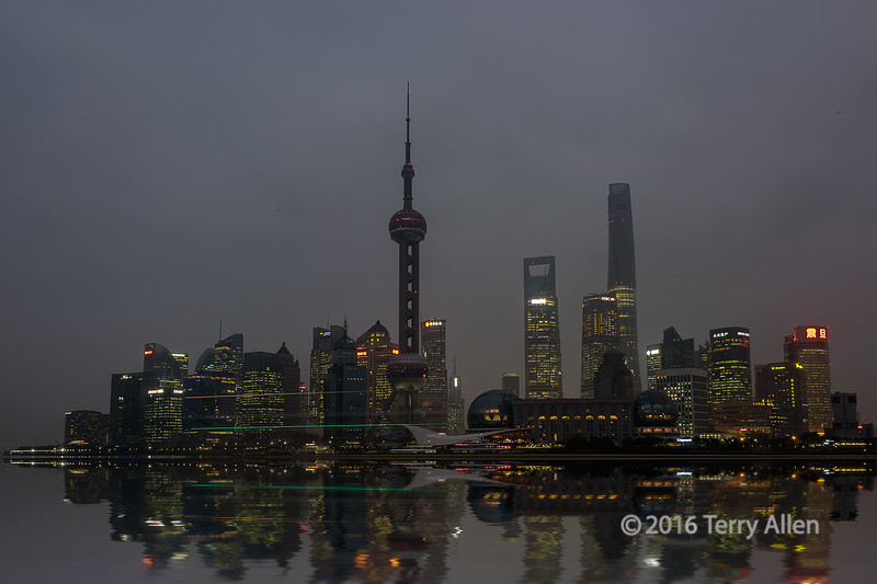 """Night lights (best largest)<br /> <br /> There is a lot going on in this photo of the Pudong skyline in the late evening.  <br /> <br /> First, the story of why so few buildings are lit up....at New Year's there was a number of deaths when the crowds panicked in the crowded viewing stands while viewing the fireworks over Pudong, so the famous lights of Pudong were turned off in mourning.  <br /> <br /> Second, this was a very long exposure (30 sec) made possible by setting the ISO as its lowest value (64), setting the aperture at a very high value (f22) and using a 6 stop neutral density filter to hold back the light so the river would go smooth.<br /> <br /> Third, a freighter went through the scene as the shutter was open, so the streaks of light are from its mast head running light (yellow streak) and the starboard running light (green).<br /> <br /> Fourth, the extremely tall building in the background is the Shanghai tower, the 2nd tallest building in the world.  They now have the lower two-thirds of the building finished and lit up inside and it will be completed soon, according to one of the building architects I talked to on the flight over.<br /> <br /> Fifth, I used a flood filter to put reflections of the skyline in the smooth water to add a little pizzaz since the skyline was darker than usual and didn't reflect well.<br /> <br /> A couple more shots from Shanghai can be seen here: <a href=""""http://goo.gl/aIqHP9"""">http://goo.gl/aIqHP9</a><br /> <br /> 17/02/15  <a href=""""http://www.allenfotowild.com"""">http://www.allenfotowild.com</a>"""