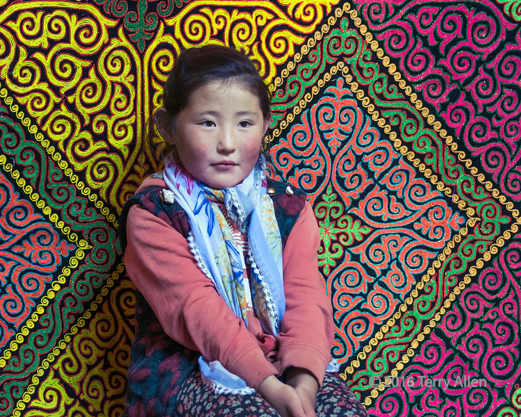 """Rosy-cheeked girl<br /> <br /> This little girl is the daughter of a Kazakh eagle hunter seen in another photo posted today.  She was very shy so I spent some time hanging around with her until she was comfortable posing for me in front of the embroidered hangings that line her parent's ger.<br /> <br /> Photos of her dad and other eagle hunters can be seen here: <a href=""""http://goo.gl/EBG7kM"""">http://goo.gl/EBG7kM</a><br /> <br /> 24/03/15  <a href=""""http://www.allenfotowild.com"""">http://www.allenfotowild.com</a>"""
