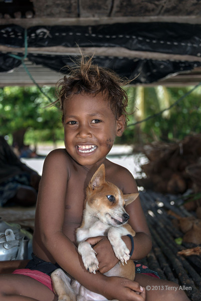 """Boy and his puppy in the family hut, Bodauna Is, Laughlan Islands, PNG<br /> <br /> The Laughlan Islands are a small group of islands (hard to find, even on Google Earth.  Hint, search for Bodelun Island to the ESE of Woodlark Island).  They are the outermost part of the Kula Ring.<br /> <br /> I'm off tomorrow to explore my 'back yard', the Great Bear Rainforest  <a href=""""http://www.britishcolumbia.com/regions/towns/?townid=4120"""">http://www.britishcolumbia.com/regions/towns/?townid=4120</a>) and the Fiordland Conservancy  <a href=""""http://www.britishcolumbia.com/parks/?id=24"""">http://www.britishcolumbia.com/parks/?id=24</a>. This is one of the largest remaining tracts of unspoiled temperate rainforest in the world. The area is home to grizzly bears, humpback whales, cougars, wolves, salmon, and the Kermode (""""spirit"""") bear, a unique subspecies of the black bear, in which one in ten cubs display a recessive white coloured coat.  This area also contains the traditional territories of three First Nations Peoples, the Heltsiuk,the Kitasoo/Xai'xais, and the Gitga'at People.  <br /> <br /> There is no internet of cell phone service throughout most of this area, so I won't be posting or commenting until my return, when my Melanesian series will continue, interspersed with (hopefully) interesting photos from the coastal fjords of BC. <br /> <br /> I have made the whole Kitava Island gallery public for those who might want to browse them during my absence: <a href=""""http://goo.gl/7nbxI"""">http://goo.gl/7nbxI</a>, and if you have time to leave a comment, even better!"""