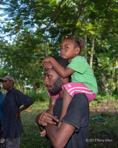 """Father carrying daughter on his shoulders, Santa Ana Island, Solomon Islands<br /> <br /> The father was busy watching the dancers, but his child was more interested in me and my camera.<br /> <br /> Another photo of a father and child, and some photos of women dancers can be seen here: <a href=""""http://goo.gl/vQoBmP"""">http://goo.gl/vQoBmP</a><br /> <br /> 12/12/13  <a href=""""http://www.allenfotowild.com"""">http://www.allenfotowild.com</a>"""