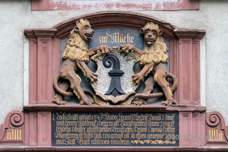 """Seen on an old building.<br /> <br /> Two lions holding the Basel City coat of arms with a black bishop's crozier on a white field.  No idea why they're sticking their tongues out, but this is not uncommon on lions in heraldry ....anyone know why?<br /> <br /> For a medieval door and a bas relief see here: <a href=""""http://goo.gl/jUkif2"""">http://goo.gl/jUkif2</a><br /> <br /> 16/10/13  <a href=""""http://www.allenfotowild.com"""">http://www.allenfotowild.com</a>"""