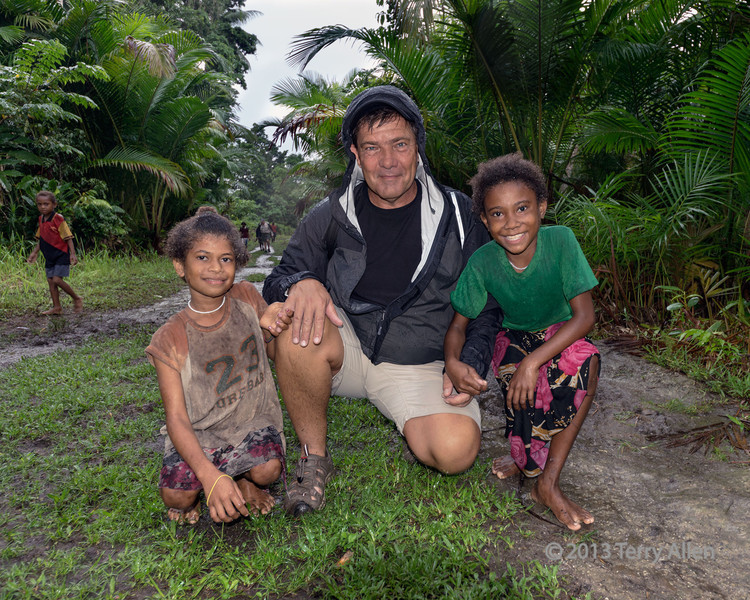 """Wrestler with two little girls, Fergusson Is, D'Entrecasteaux Islands, PNG<br /> <br /> S. is a retired pro wrestler and the children gravitated to him wherever we went.  These two little girls grabbed hold of his fingers and didn't let go once the entire walk to the hot springs.  Another photo taken in the rain, which is actually better for getting good colour than bright sun.<br /> <br /> See other pics from Fergusson Island here: <a href=""""http://goo.gl/0u7pH"""">http://goo.gl/0u7pH</a>"""