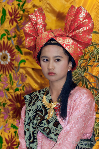 "Portrait of a Minangkabau girl at a wedding feast, Cupek, West Sumatra<br /> <br /> I posed this pretty young woman wearing traditional dress against one of the colourful wall hangings that decorated the Chief Regent's house.<br /> <br /> Update in response to comments: I noticed that it appeared to be the accepted norm among the Minangkabau people to adapt a serious, non-smiling pose when they are posing for portraits, although I have a number of casual photos when they are in a group where they relax and smile and ham it up (upcoming posts),  You can also see this serious demeanour in the wedding photos I posted a few days ago, seen here <a href=""http://goo.gl/O9Mzzh"">http://goo.gl/O9Mzzh</a> and in portraits to come.<br /> <br /> More photos from West Sumatra can be seen here: <a href=""http://goo.gl/zRM7QE"">http://goo.gl/zRM7QE</a>"
