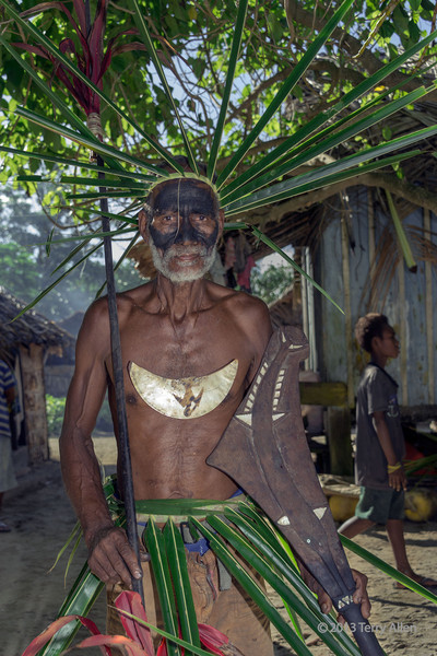 """Portait of a warrior-7, Santa Ana Island in the <br /> Santa Cruz Islands, Solomon Islands<br /> <br /> This warrior is wearing a pearl shell Dafi or Tema (means chest ornament) with frigate bird overlay. Dafi shell jewelry is similar to kina shell jewelry in New Guinea.  He is carrying a wooden parrying shield with a carved fish (probably hound needlefish) on it<br /> <br /> Other warrior portraits can be seen here: <a href=""""http://goo.gl/nAQ5j3"""">http://goo.gl/nAQ5j3</a><br /> <br /> 9/12/13  <a href=""""http://www.allenfotowild.com"""">http://www.allenfotowild.com</a>"""