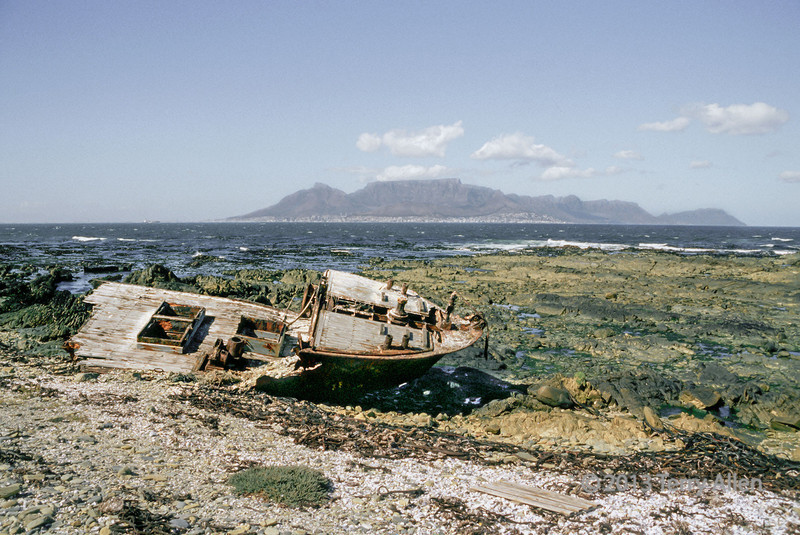 """Wrecked fishing boat on Robben Island, Cape Town in background, South Africa<br /> <br /> Taken from my archives and posted today in memory of Nelson Mandela, the remarkable South African who died yesterday at the age of 95.<br /> <br /> I first visited South Africa in 1984 when it was still  under the apartheid regime, and Nelson Mandela was imprisoned on Robben Island off the south coast of Cape Town.  I visited again in 2000 after the Truth and Reconciliation hearings and made a trip to Robben Island to see the prison there and the cell where Mandela had been imprisoned for much of his 27 years in prison.  I took this picture on the beach of Robben Island and I like to think that Madiba may have stood on this very spot by the old wrecked boat and enjoyed this view of Cape Town.<br /> <br /> In the winter of 1964, Nelson Mandela arrived on Robben Island where he would spend 18 of his 27 prison years. Confined to a small cell, the floor his bed, a bucket for a toilet, he was forced to do hard labor in a quarry. He was allowed one visitor every 6 months for 30 minutes. He could write and receive one letter of 500 words every six months. But Robben Island became the crucible which transformed him. Through his intelligence, charm and dignified defiance, Mandela eventually bent even the most brutal prison officials to his will, assumed leadership over his jailed comrades and became the master of his own prison. He emerged from it the mature leader who would fight and win the great political battles that would create a new democratic South Africa.  Mandela was released from Robben Island in 1990 and four years later the prisoner became the President. Adapted from <a href=""""http://www.pbs.org/wgbh/pages/frontline/shows/mandela/prison/"""">http://www.pbs.org/wgbh/pages/frontline/shows/mandela/prison/</a><br /> <br /> A panorama of Cape Town taken from the boat to Robben Island can be seen here: <a href=""""http://goo.gl/KLboKD"""">http://goo.gl/KLboKD</a><br /> <br /> 06/11/13  <a """