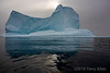 Iceberg with rising sun and reflections