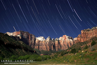 "July 3rd - ""Towers of the Virgin""  Zion National Park, UT Zion National Park has some of the most amazing and rugged mountains and cliffs you will see anywhere.  This particular location is just behind the visitor center as you enter the park from the South.  A friend and I sat here for two hours shooting star trails with the full moon behind us to get this image.  Technical Details: Shot with Canon 10D and Canon 20mm lens at F2.8 and 30 seconds."
