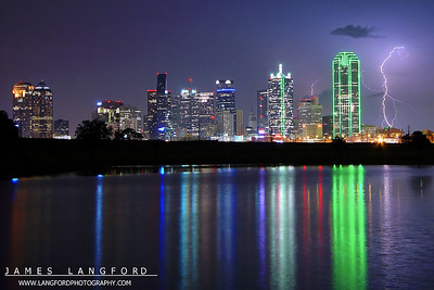 """June 21th - """"Towers of Light""""  Dallas, TX This shot was pretty much a complete accident.  I was downtown shooting the skyline reflection and noticed this storm off on the horizon.  I was quickly able to frame this scene and captured the lucky strike in this position. Technical Details: Shot with Sony F707 at F4 and 8 seconds."""