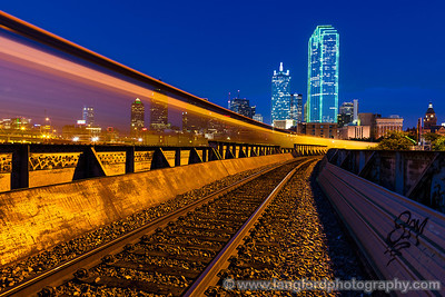 "July 24th - ""Just Passin' Through""  Dallas, TX A good friend shared this location for shooting the Dallas skyline with me yesterday.  What a view!  It was made even better when a freight train passed by.  The cars had gaps in them allowing the skyline to show through. Technical Details: Shot with a Canon 5d Mk2 and a Canon 24-70mm lens at F10 and 30 seconds."