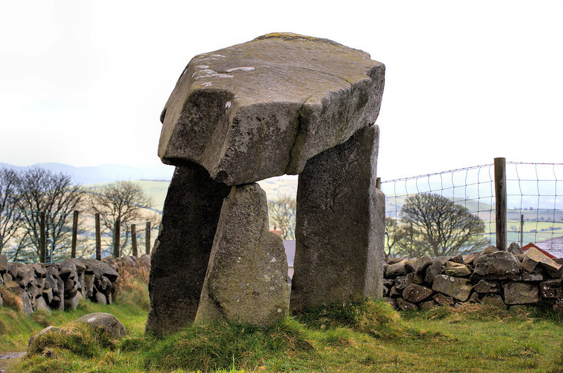 "Legananny Dolmen<br /> <br /> Legananny Dolmen is a megalithic dolmen or cromlech nine miles southeast of Banbridge and three miles north of Castlewellan, both in County Down, Northern Ireland. It is on the slopes of Slieve Croob near the village of Leitrim, in Drumgooland parish, nestled between the farmer's stone wall and a back road. It is a State Care Historic Monument sited in the townland of Legananny, in Banbridge District, at grid ref: J2887 4339.<br /> <br /> This tripod dolmen has a capstone over 3m long and 1.8m from the ground. It dates to the Neolithic period, making the monument approximately 5,000 years old. Such portal tombs were funerary sites for the disposal of the dead in Neolithic society. The heavy stones would have been dragged some distance before being set in place. The three supporting stones are unusually long and there are slight traces of a cairn which must have been far more extensive. Some urns were found underneath. (Courtesy Wikipedia)<br /> <br /> <br /> The name Legananny is believed to be derived from Irish Liagán Áine, meaning ""Áine's standing stone"" – Áine being an Irish goddess.<br /> <br /> Post date: 8th October 2013"