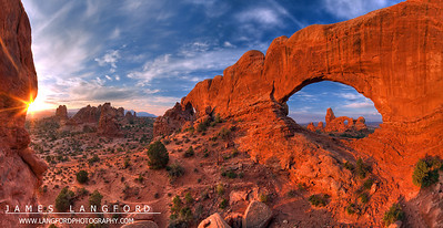 "July 11th - ""Turret Arch""  Arches National Park, UT It is possible to capture Turret Arch through The North Windows arch, creating this amazing scene.  To get to this location, you have to climb through the North Window and scramble up some rocks.  This is one of the best views within Arches National Park, in my opinion. Technical Details: Shot with a Canon 5d Mk2 and a Canon 20mm prime lens at F16.  Bracketted images stitched and merged to create a wider dynamic range."