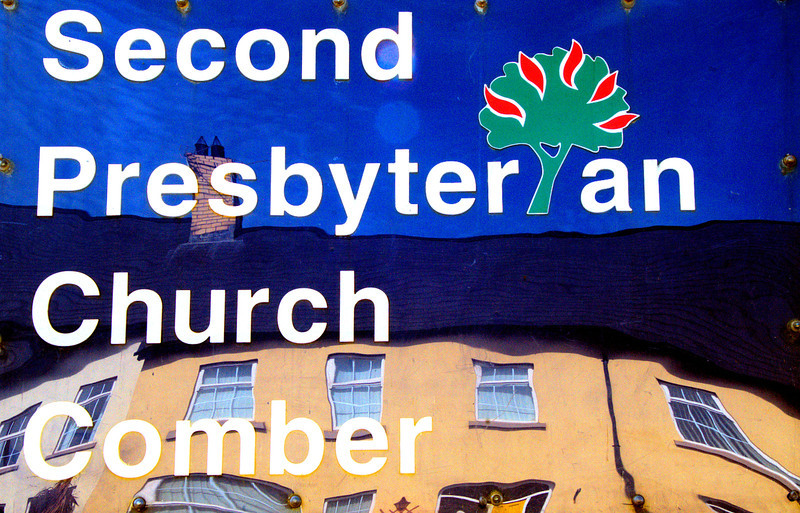 Church sign with reflected buildings