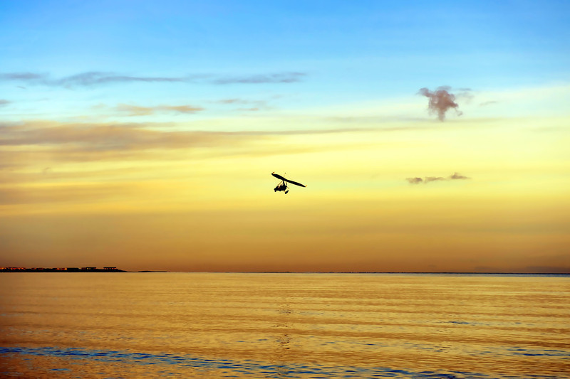 A motorised hang glider flies low over Cloughey beach at dusk on 2/2/2013