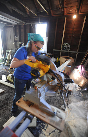 Olivia Nichol uses a power saw to cut a 2x4 for their handicap ramp the group at the 610 Vickroy street location is working on