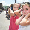 Sydney Rhoades,6, of Durham, NC., left, and cousin Marina Yarnavick, 7, of Winder, protect their ears while the parade moves down Main St.