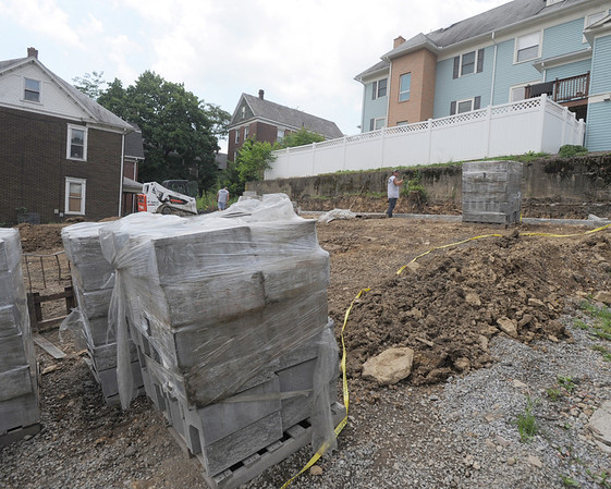 Milkie's employees Josh Shauley (foreground) and Dave Christina work on the new retaining wall